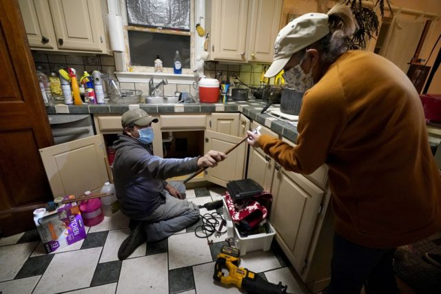 In this Feb. 20, 2021, file photo, Handyman Roberto Valerio, left, hands homeowner Nora Espinoza the broken pipe after removing it from beneath her kitchen sink in Dallas. The pipe broke during freezing temperatures brought by last week's winter weather. (AP Photo/Tony Gutierrez, File)