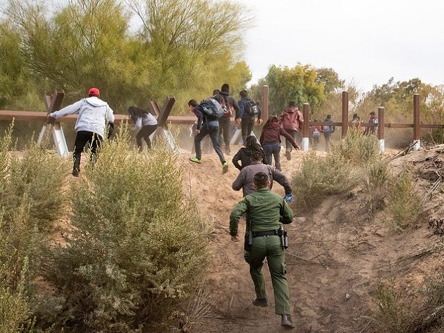 A Yuma Sector Border Patrol agent chases a group of migrant in an unsecured section of the Arizona border. (File Photo: U.S. Border Patrol/Jerry Glaser)