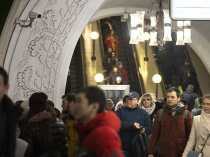In this photo taken on Saturday, Feb. 22, 2020, a surveillance camera, top left, is seen as people walk down in a Moscow's Metro (subway) station in Moscow, Russia. Metro workers were instructed to stop passengers from China and ask them to fill out a questionnaire about the purpose of …