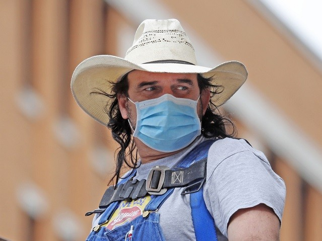 An unidentified man wears a mask and cowboy hat amid concerns of COVID-19 spreading as he works atop a lift in downtown Dallas, Tuesday, March 31, 2020. For most people, the coronavirus causes mild or moderate symptoms, such as fever and cough that clear up in two to three weeks. …