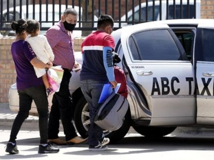 Larissa Bautista Hernandez, 2, second from left, a migrant from Honduras, is carried by her mother, Irma Hernandez, left, as her father, Jose Frankis Bautista, right, heads into a taxi cab at a bus station, Wednesday, March 17, 2021, in Brownsville, Texas. The family is seeking asylum from the U.S. …