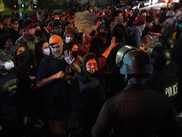 Demonstrators face off with police in the Echo Park section of Los Angeles Thursday, March 25, 2021. Demonstrators gathered Wednesday night to protest the planned temporary closure of a Los Angeles park that would displace a large homeless encampment, which has grown throughout the coronavirus pandemic. (AP Photo/Marcio Jose Sanchez)