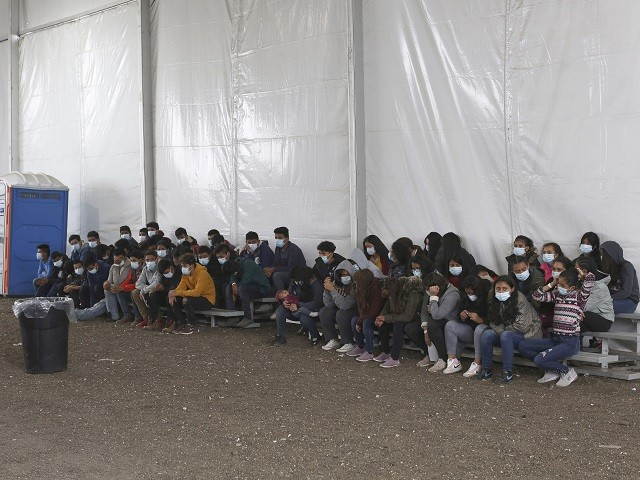 Newly migrants wait to enter the intake area at the Donna Processing Center, run by the U.S. Customs and Border Patrol (CBP), the main detention center for unaccompanied children in the Rio Grande Valley, in Donna, Texas, Tuesday, March 30, 2021. (AP Photo/Dario Lopez-Mills, Pool)