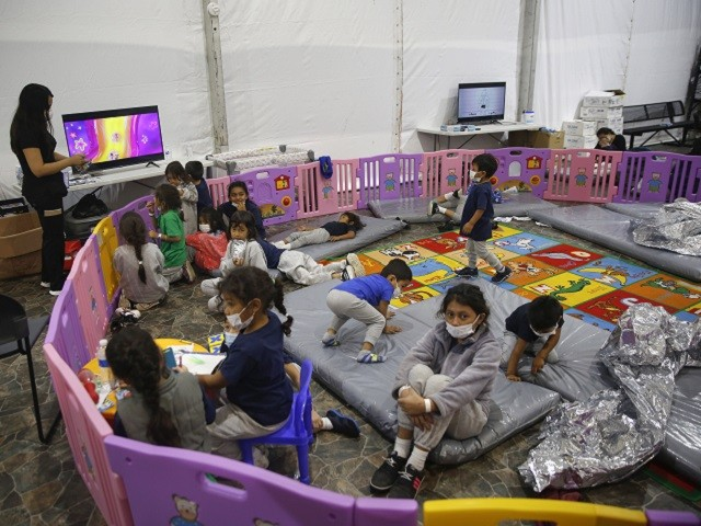 Monitored by a caretaker, young unaccompanied migrants, aged from 3 to 9, watch television inside a playpen at the U.S. Customs and Border Protection facility, the main detention center for unaccompanied children in the Rio Grande Valley, in Donna, Texas, Tuesday, March 30, 2021. The youngest of the unaccompanied minors are kept separate from the rest of the detainees. (AP Photo/Dario Lopez-Mills, Pool)