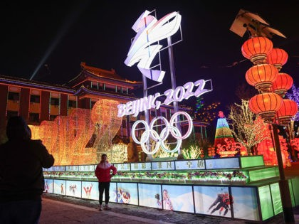 BEIJING, CHINA - FEBRUARY 26: People wear protective masks as they walk front the logos of the 2022 Beijing Winter Olympics at Yanqing Ice Festival on February 26, 2021 in Beijing, China. The Festival comes at the final day of the Chinese Lunar New Year celebrations. (Photo by Lintao Zhang/Getty …