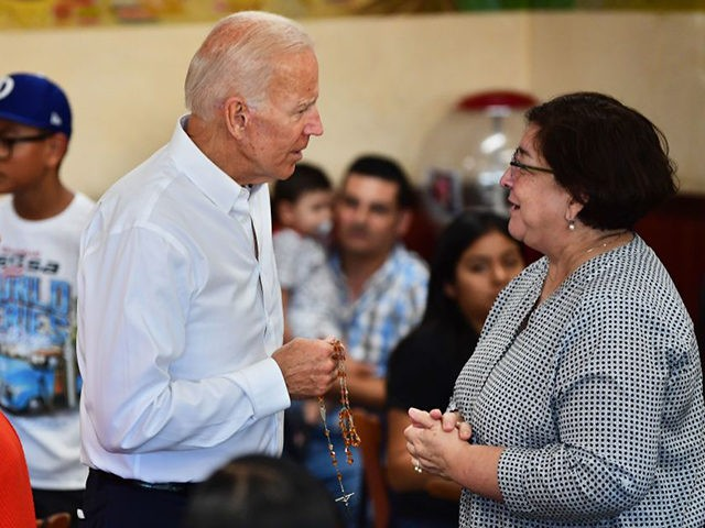 Democratic party candidate Joe Biden is given a rosary while meeting with patrons, alongside Hilda Solis (L), Former United States Secretary of Labor and a member of the Los Angeles County Board of Supervisors, of Tamales Lilianas restaurant in Los Angeles, California on July 19, 2019. - Democrats are gearing …