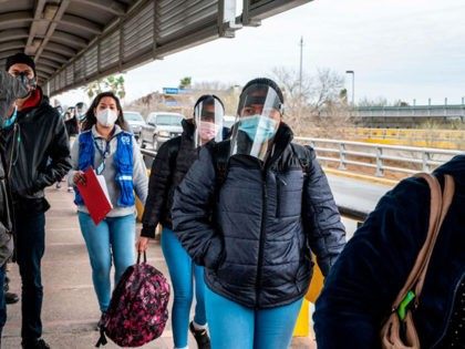 Migrants approach the US border on Gateway International Bridge in Brownsville, Texas on March 2, 2021. - President Biden announced that he was ending the Migrant Protection Protocol (MPP) enacted under President Trump that sent asylum seekers back to Mexico as they awaited their trial dates. (Photo by Sergio FLORES …