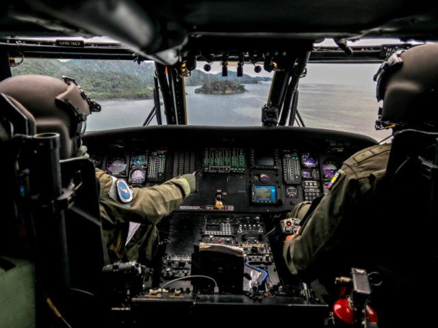 Colombian Air Force pilots fly a blackhawk helicopter over the Gulf of Uraba during a surveillance mission in which also school kits and humanitarian aid were distributed, in Choco department, Colombia, near the border with Panama, on October 14, 2020, amid the new coronavirus pandemic. (Photo by JOAQUIN SARMIENTO / …