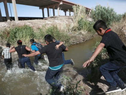 Migrants scramble across the Rio Bravo to surrender to the American authorities, on the US - Mexico border between Ciudad Juarez and El Paso, Saturday, June 15, 2019. (AP Photo/ Photo/Christian Torres)