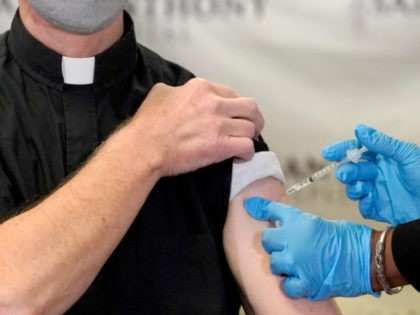 In this Wednesday, Dec. 23, 2020 file photo, a Catholic pastor receives the first of the two Pfizer-BioNTech COVID-19 vaccinations at a hospital in Chicago. In a growing consensus, religious leaders at the forefront of the anti-abortion movement in the United States are telling their followers that the leading vaccines …