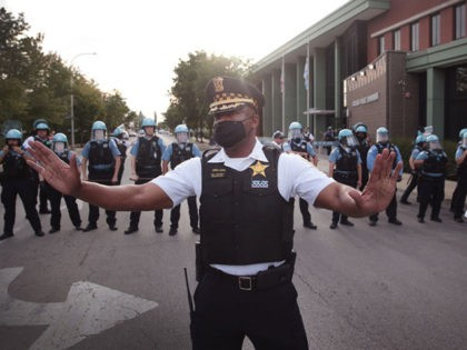 CHICAGO, ILLINOIS - AUGUST 11: A Chicago police officer attempts to deescalate tension as Englewood residents clash with demonstrators protesting outside the 7th District station of the Chicago Police Department on August 11, 2020 in Chicago, Illinois. The protest was held in response to the August 9 shooting and wounding …