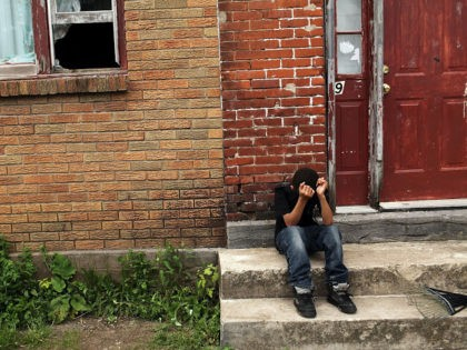 UTICA, NY - MAY 14: A child sits on a stoop in a working class section of Utica on May 14, 2012 in Utica, New York. Like many upstate New York communities, Utica is struggling to make the transition from a former manufacturing hub. The city's individual poverty rate is …