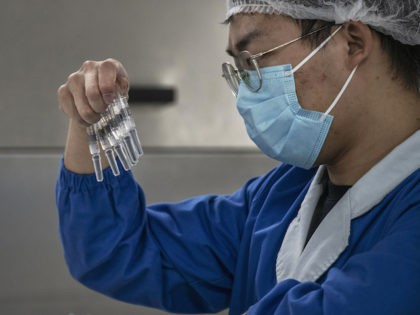 A worker checks syringes of the potential vaccine CoronaVac on the production line at Sinovac Biotech where the company is producing their potential COVID-19 vaccine CoronaVac on September 24, 2020 during a media tour in Beijing, China. (Kevin Frayer/Getty Images)