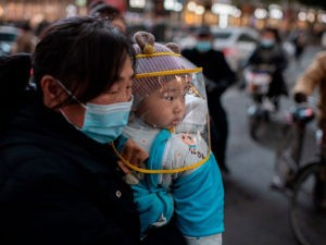 TOPSHOT - A woman wearing a face mask holds a baby that wears a protective shield during rush hour on a street outside of a shopping mall complex in Wuhan on January 13, 2021. - A team of WHO experts will land directly in Wuhan on January 14, 2021, China's foreign ministry said, starting their long-delayed probe into Covid-19 at the virus epicentre. (Photo by NICOLAS ASFOURI / AFP) (Photo by NICOLAS ASFOURI/AFP via Getty Images)
