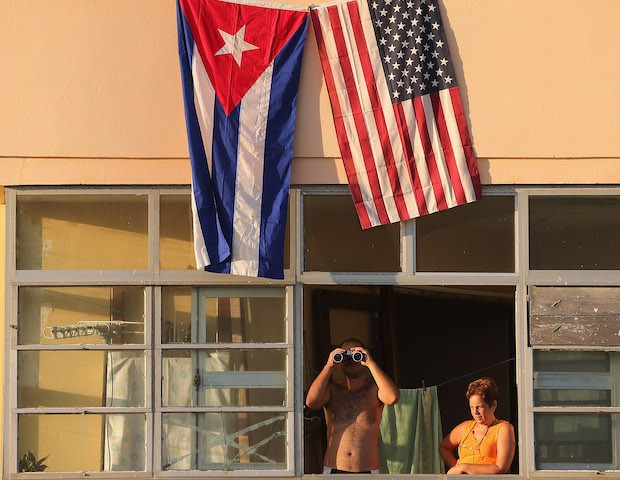 Cubans look out their window across the street from the newly reopened U.S. Embassy in hopes of watching the flag-raising ceremony August 14, 2015 in Havana, Cuba. The first American secretary of state to visit Cuba since 1945, Secretary of State John Kerry visited the reopened embassy, a symbolic act …