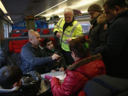 PADBORG, DENMARK - JANUARY 06: A Danish policeman checks the identity papers of passengers on a train arriving from Germany on January 6, 2016 in Padborg, Denmark. Denmark introduced a 10-day period of passport controls and spot checks on Monday on its border to Germany in an effort to stem …