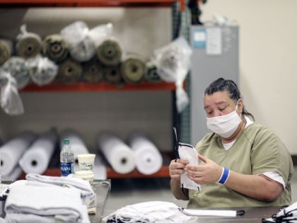 An inmate sews protective masks at Las Colinas Women's Detention Facility in Santee, California, on April 22, 2020. - Inmates and Sheriff's deputies at the prison are practicing COVID-19 measures including wearing masks, staying keeping a safe distance and doing more frequent cleaning at the facility. (Sandy Huffaker/AFP via Getty …
