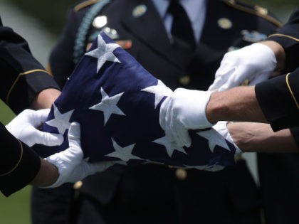 """Members of the U.S. Army's 3rd Infantry Regiment """"The Old Guard"""" fold a flag during the funeral of World War II Army veteran Carl Mann on the 75th anniversary of the D-Day invasion June 6, 2019 at Arlington National Cemetery in Arlington, Virginia. (Alex Wong/Getty Images)"""
