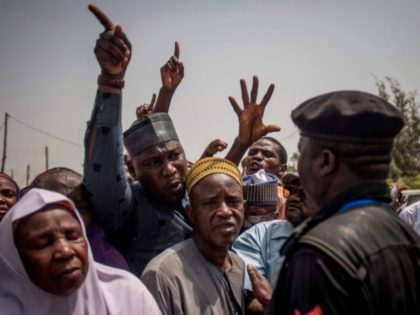 People talk to a policeman at Badarawa Junction polling station in Kaduna on February 23, 2019. - Nigerians began voting for a new president on February 23, after a week-long delay that has raised political tempers, sparked conspiracy claims and stoked fears of violence. Some 120,000 polling stations began opening …