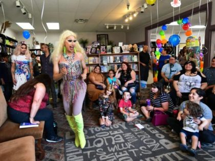 Drag queens Athena Kills (C) and Scalene Onixxx arrive to awaiting adults and children for Drag Queen Story Hour at Cellar Door Books in Riverside, California on June 22, 2019. - Athena and Scalene, their long blonde hair flowing down to their sequined leotards and rainbow dresses, are reading to …