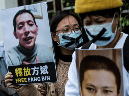 A pro-democracy activist (C) from HK Alliance holds a placard of missing citizen journalist Fang Bin, as she protests outside the Chinese liaison office in Hong Kong on February 19, 2020, in protest against Beijings detention of prominent anti-corruption activist Xu Zhiyong. - Police in China have arrested Xu Zhiyong, …