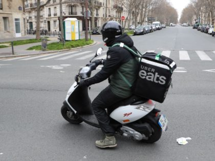 An Uber Eats delivery man rides a moped in Paris on March 22, 2020, as a strict lockdown is in effect to limit the spread of the COVID-19 caused by novel coronavirus in the country prohibiting all but essential outings. (Photo by Ludovic MARIN / AFP) (Photo by LUDOVIC MARIN/AFP …