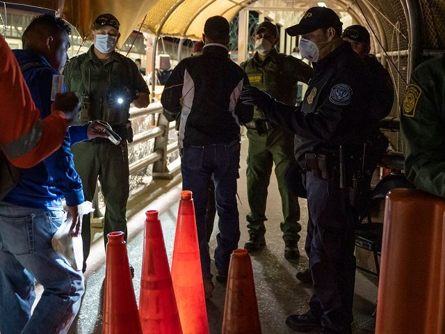 US Customs and Border Protection and Border Patrol agents wearing masks for protection against COVID-19 check pedestrians IDs on April 1, 2020, on the Paso del Norte International Bridge between Ciudad Juarez, Mexico and El Paso, Texas. - Both Ciudad Juarez and El Paso, Texas, are on stay-at-home orders, but …