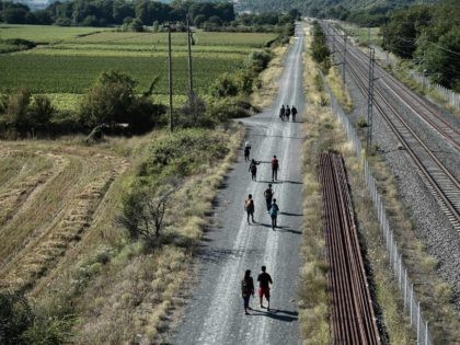 Migrants walk along rail tracks near Idomeni at the border between Greece and North Macedonia on July 16, 2020. - Four years after the evacuation of the Idomeni camp, many refugees and immigrants choose the same route again, trying to leave Greece and find themselves in other European countries. Many …