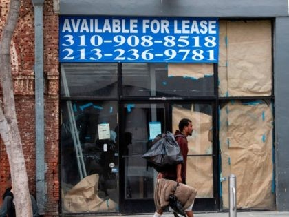 "A homeless person walks by a closed business with a sign reading ""For Lease"" in Santa Monica, California, on July 28, 2020, amid the coronavirus pandemic. (Photo by VALERIE MACON / AFP) (Photo by VALERIE MACON/AFP via Getty Images)"