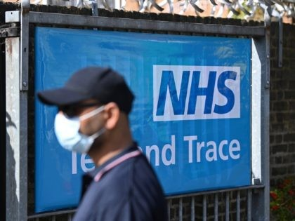 A worker wearing a face mask or covering due to the COVID-19 pandemic, stands near a sign for Britain's NHS (National Health Service) Test and Trace service, as he works at the entrance to a novel coronavirus walk-in testing centre in East Ham in east London, on September 17, 2020. …