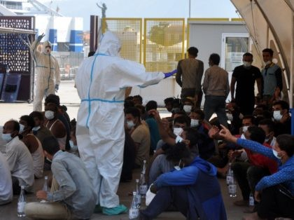 A group of migrants receive food and water from rescuers on September 17, 2020 in the port of Palermo, Sicily, after a patrol boat of the Italian Coast Guards (Guardia Costiera) rescued them towards the port of Palermo, after a group of 76 migrants threw themselves into the sea from …