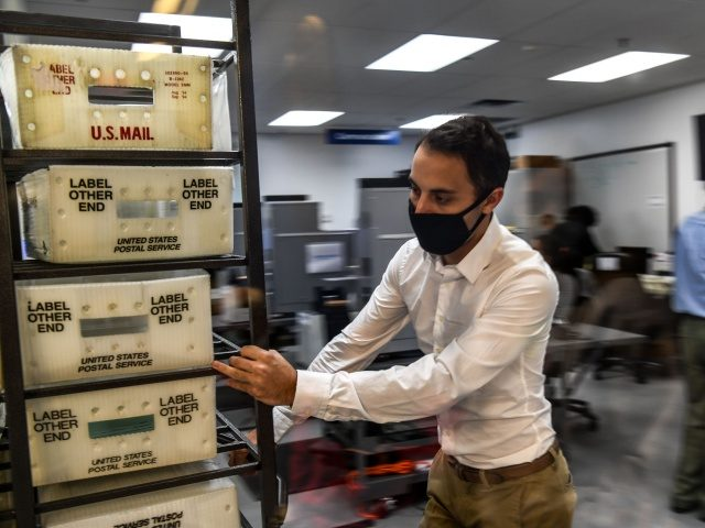Electoral workers are seen during the vote-by-mail ballot scanning process at the Miami-Dade County Election Department in Miami, Florida on November 3, 2020. - The US started voting Tuesday in an election amounting to a referendum on Donald Trump's uniquely brash and bruising presidency, which Democratic opponent and frontrunner Joe …