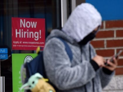"A man wearing a face mask stands next to a ""Now Hiring "" sign in front of a store on December 18, 2020, in Arlington, Virginia . - US lawmakers were hammering out final details on a major coronavirus relief package and an attached federal funding bill but sticking points …"