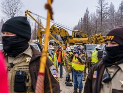 Construction workers stand behind Aitkin County sheriff officers as environmental activist protest at the construction site for the Line 3 oil pipeline site near Palisade, Minnesota on January 9, 2021. - Line 3 is an oil sands pipeline which runs from Hardisty, Alberta, Canada to Superior, Wisconsin in the United …