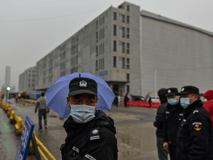 A guard control the access to the Baishazhou market as members of the World Health Organization (WHO) team, investigating the origins of the Covid-19 coronavirus, arrive at the market in Wuhan, China's central Hubei province on January 31, 2021. (Photo by Hector RETAMAL / AFP) (Photo by HECTOR RETAMAL/AFP via …