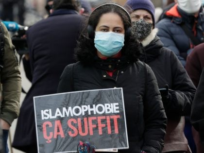"A woman holds a placard reading ""enough of islamophobia"" as protesters demonstrate against a bill dubbed as ""anti-separatism"", in Paris on February 14, 2021. - French lawmakers a few weeks ago began debating a controversial bill against what the interior minister described as the ""disease"" of Islamist extremism eating away …"