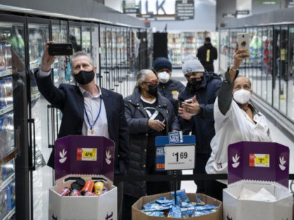 WASHINGTON, DC - FEBRUARY 25: Grocery store workers and shoppers try to get a glimpse of U.S. Vice President Kamala Harris as she visits the pharmacy of a Giant Foods grocery store to promote the Biden Administrations Federal Retail Pharmacy Program for COVID-19 vaccination on February 25, 2021 in Washington, …