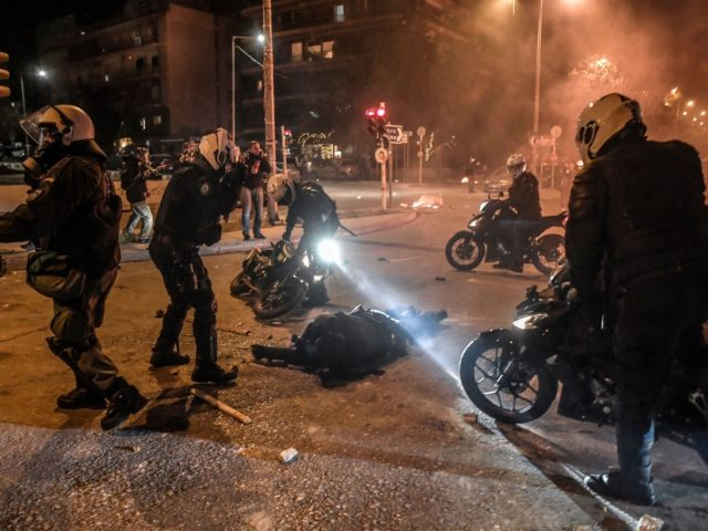 Motorised police arrive to tend to their injuried colleague during a demonstration against police violence in an Athens suburb on March 9, 2021. - Greek police said an officer was seriously injured in the head as clashes broke out March 9 evening at a protest of some 5,000 people in …