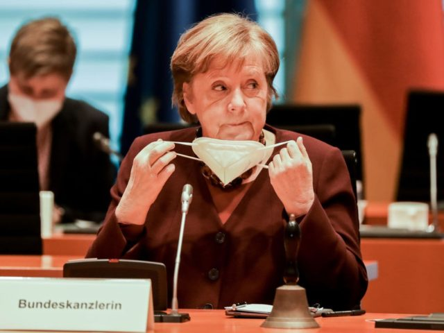 BERLIN, GERMANY - MARCH 10: German Chancellor Angela Merkel puts out a face mask as she attends the weekly meeting of the German Federal cabinet in the conference hall of the Chancellery on March 10, 2021 in Berlin, Germany. (Photo by Poly Styrene - Pool/Getty Images)