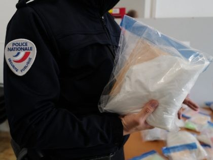 A French police officer holds cocaine sacks, after a seizure of drugs in Nice, on March 19, 2021. (Photo by Valery HACHE / AFP) (Photo by VALERY HACHE/AFP via Getty Images)