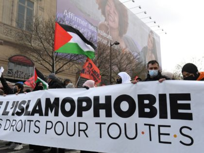 "Protesters hold a banner and a Palestinian flag during a demonstration against a bill dubbed as ""anti-separatism"" and islamophobia in Paris on March 21, 2021. - A divisive debate takes place in France about what French President has termed ""Islamist separatism,"" in which Islamists are said to be flouting French …"