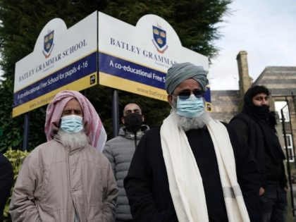 BATLEY, ENGLAND - MARCH 26: People gather outside the gates of Batley Grammar School, after a teacher was suspended for showing an image of the Prophet Muhammad in class, on March 26, 2021 in Batley, England. A few dozen people, including parents of students, gathered outside the school gates yesterday …
