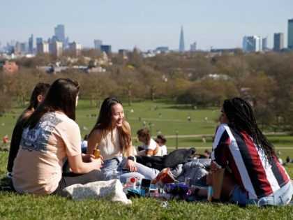A group sit and chat in the warm weather on Primrose Hill in London on March 29, 2021, as England's third Covid-19 lockdown restrictions ease, allowing groups of up to six people to meet outside. - England began to further ease its coronavirus lockdown on Monday, spurred by rapid vaccinations, …