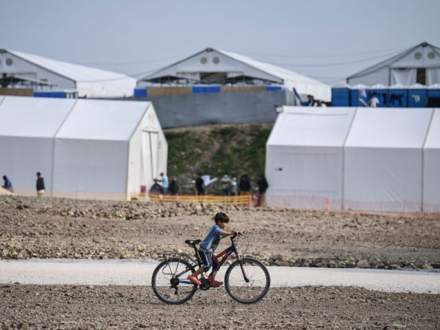 A child rides a bicycle inside the new refugee camp of Kara Tepe in Mytilene, on Lesbos, on March 29, 2021. - EU home affairs commissioner Ylva Johansson pledged 276 million euros ($326 million) of EU money for new camps on the islands of Lesbos, Chios, Samos, Kos and Leros, …