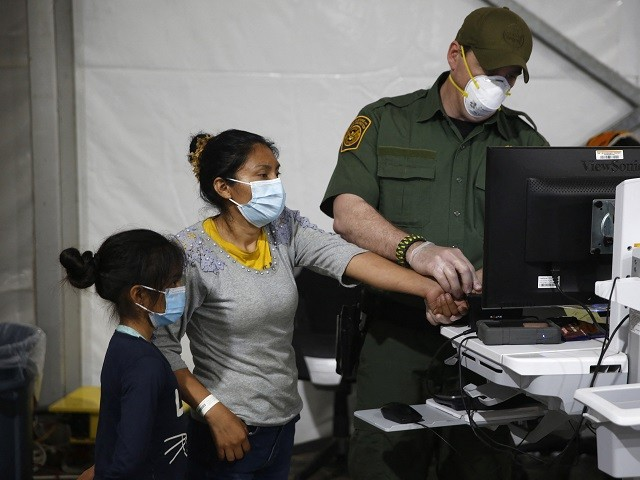 A migrant and her daughter have their biometric data entered at the intake area of the Donna Department of Homeland Security holding facility, the main detention center for unaccompanied children in the Rio Grande Valley in Donna, Texas on March 30, 2021. (Photo by Dario Lopez-Mills / POOL / AFP) (Photo by DARIO LOPEZ-MILLS/POOL/AFP via Getty Images)