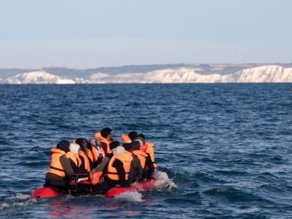 AT SEA, UNITED KINGDOM - SEPTEMBER 07: Migrants packed tightly onto a small inflatable boat attempt to cross the English Channel near the Dover Strait, the world's busiest shipping lane, on September 07, 2020 off the coast of Dover, England. Last Wednesday, more than 400 migrants made the journey from …