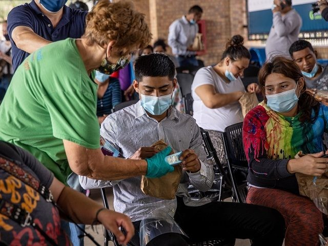 BROWNSVILLE, TEXAS - FEBRUARY 25: Immigrants receive lunch from volunteers from the immigrant assistance group Team Brownsville after a group of at least 25 asylum seekers were officially allowed to cross from a migrant camp in Mexico into the United States on February 25, 2021 in Brownsville, Texas. The group …