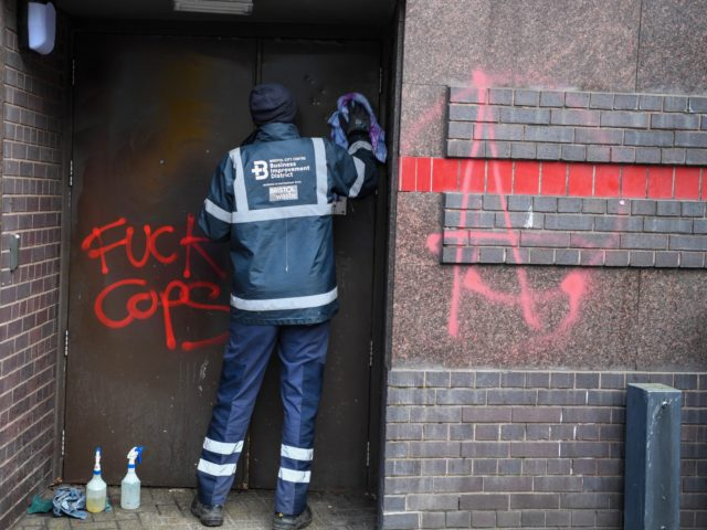 """BRISTOL, ENGLAND - MARCH 22: (EDITORS NOTE: IMAGE CONTAINS PROFANITY) Workers clean up after the protest on March 22, 2021 in Bristol, England. Protests in Bristol on Saturday at the """"Kill the Bill"""" demonstration turned violent as protestors clashed with police. Crowds had gathered for the demonstration in opposition to …"""