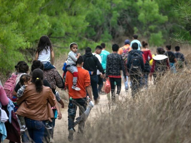 MISSION, TEXAS - MARCH 23: Asylum seekers, most from Honduras, walk towards a U.S. Border Patrol checkpoint after crossing the Rio Grande from Mexico on March 23, 2021 near Mission, Texas. A surge of migrant families and unaccompanied minors is overwhelming border detention facilities in south Texas' Rio Grande Valley. …
