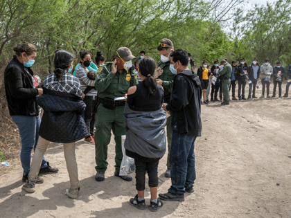 U.S. Border Patrol agents question families as a group of unaccompanied minors (R), awaits Border Patrol transport after they crossed the-Rio Grande into Texas on March 25, 2021 in Hidalgo, Texas. A large group of families and unaccompanied minors, mostly teenagers, came across the border onto private property, where Border …